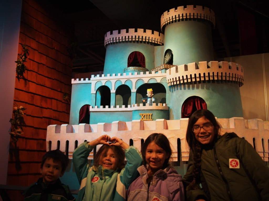 The kids stand in front of the actual castle set, from the Neighborhood of Make Believe on Mister Rogers' Neighborhood. The King Friday puppet is a replica.