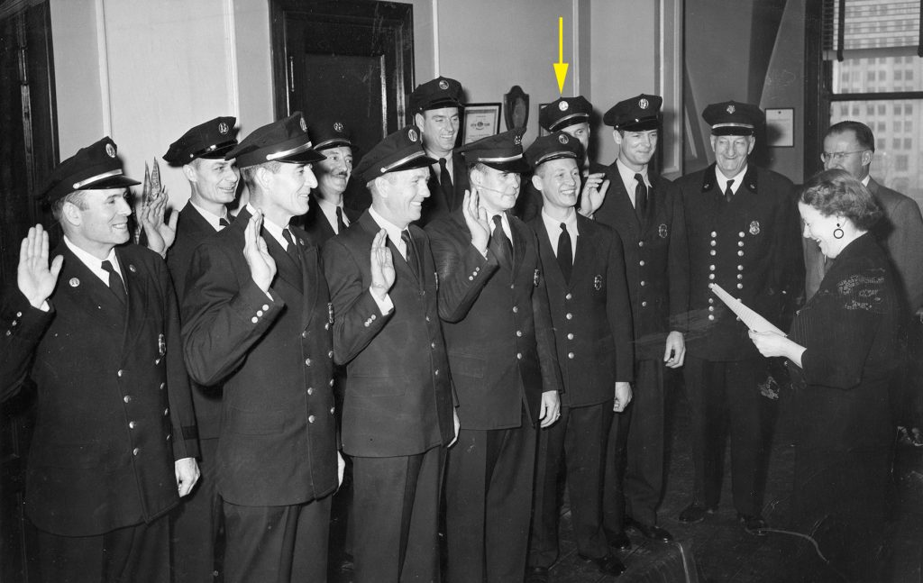 Mrs. Joseph M. Darst, city register, and men of the Fire Department enjoy the occasion as new captains and battalion chiefs are sworn in at City Hall today. In group (from left) are: Ralph E. Lowe, Joseph D. Boschert, Joseph C. Findlay, Philips T. Nix, Harry J. Wilcox, James J. O'Malley, Harvey E. Talbott, Joseph L. Nixon Jr., Frank J. Becker, Grant Berger, Chief Walter H. Kammann, Joseph P. Sestric, director of public safety, and Mrst. Darst. Lowe and Findlay are the new battalion chiefs, others are captains. (11/27/1953)